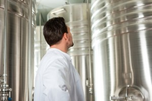 Brewer standing in his brewery in front of a stainless fermenter